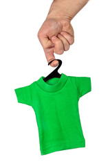 Male hand holding on finger little green T-shirt on black hanger