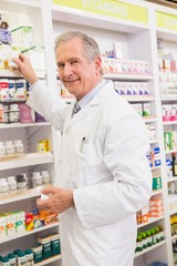 Pharmacist taking medicine from shelf