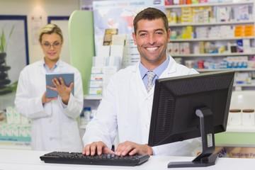 Happy pharmacist using computer