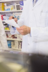 Mid section of pharmacist writing a prescription