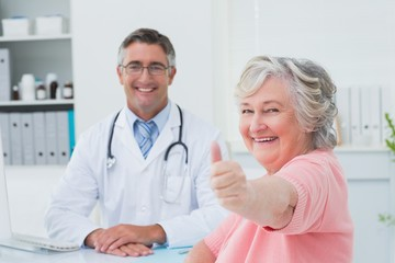 Patient showing thumbs up sign while sitting with doctor