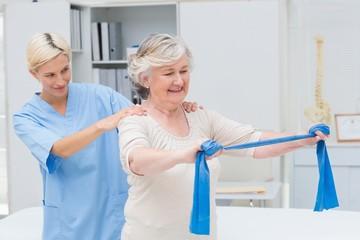 Nurse assisting senior patient in exercising