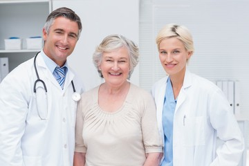 Doctors and senior patient smiling in clinic