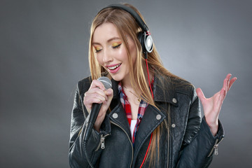 woman with headphones and microphone singing