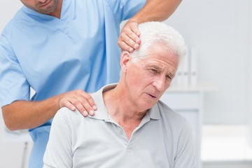 Physiotherapist giving physical therapy to senior patient