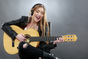 a beautiful young blonde with a classical guitar