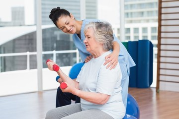 Trainer looking at senior woman lifting dumbbells