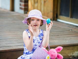 Girl Holds Up a Blue Easter Egg