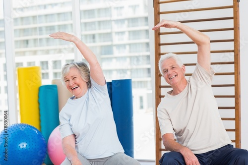 Senior couple doing stretching exercise in gym - 78830064