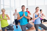 Fotoroleta People practicing tree pose in fitness studio