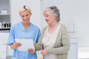 Nurse and senior patient discussing over clipboard