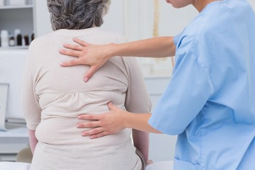 Nurse examining female patients back in clinic