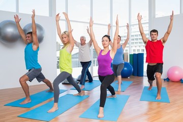 People exercising with hands raised at fitness club