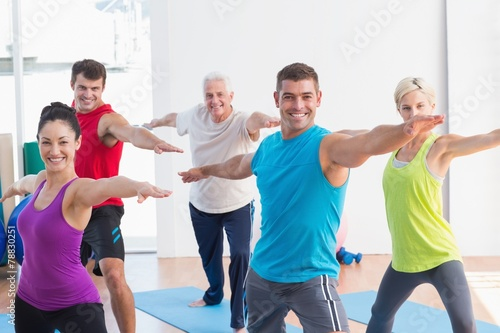 People doing warrior pose in yoga class - 78830251