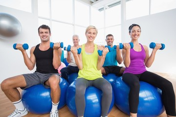 People sitting on balls and lifting weights in fitness club