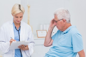 Doctor writing prescription for senior patient