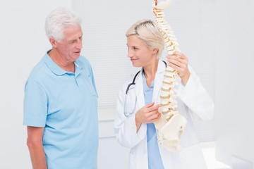 Doctor and senior patient discussing over anatomical spine