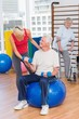 canvas print picture - Trainer assisting senior man in lifting dumbbells