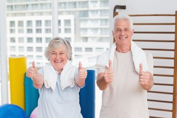 Senior couple gesturing thumbs up in gym