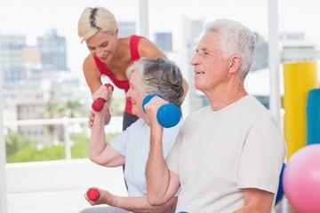 Senior man lifting dumbbells while trainer assisting