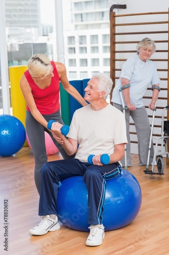 canvas print picture Trainer assisting senior man in lifting dumbbells