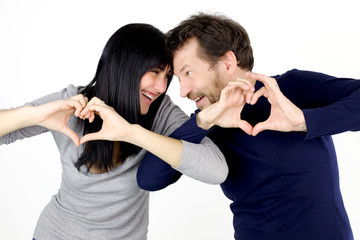 Beautiful couple playing with love sign