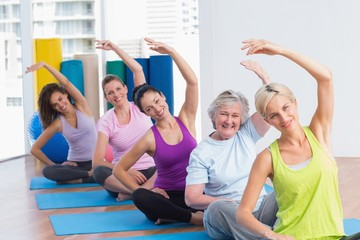 Women practicing stretching exercise in gym class