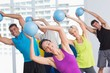 Instructor with class exercising with fitness balls - 78831068