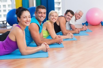 People relaxing on exercise mats in fitness studio