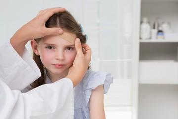 Doctor making plaster in little girl