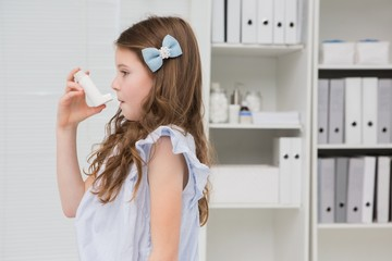Little girl taking inhaler