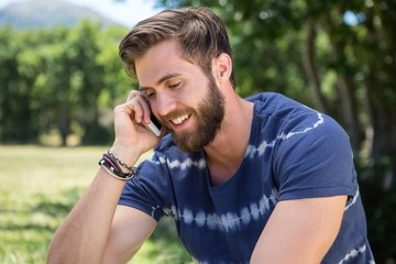 Handsome hipster on the phone in park