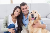 Couple with Golden Retriever in living room poster