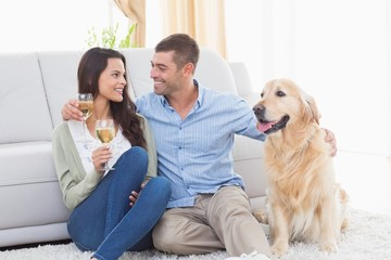 Couple holding wine glasses while sitting with dog