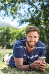 Handsome hipster using phone in park