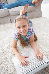 Portrait of happy girl using laptop while lying on rug