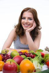 Portrait of a smiling woman sitting at the table with fruits