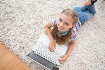 Cute girl using laptop while lying on rug
