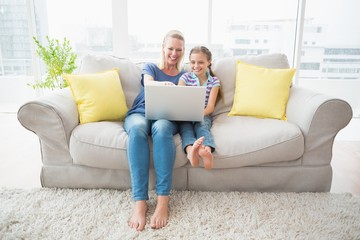 Happy mother and daughter using laptop on sofa