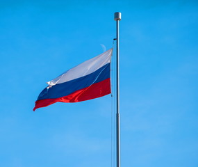 Russian State tricolor flag against the blue sky