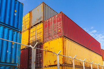 Colorful cargo containers are stacked behind metal fence