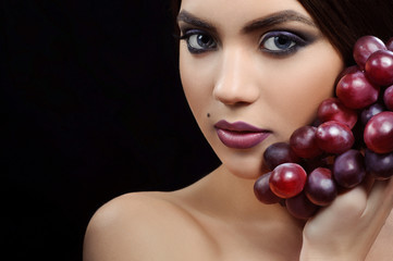 beauty portrait of a girl with makeup and grapes