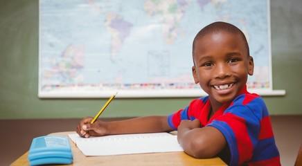 Cute little boy writing book in classroom