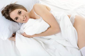 Teen in Dessous und Lingerie liegt im Bett