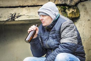 Man with beer bottle under the bridge