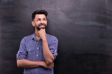 Smiling casual man on blank chalkboard background