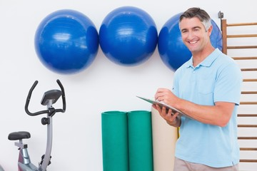 Smiling trainer writing on clipboard