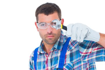 Confident repairman looking through wrench