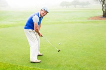 Happy golfer cheering on putting green