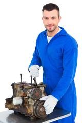 Smiling male mechanic repairing car engine